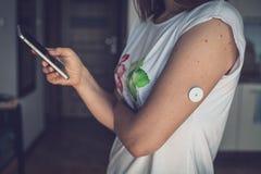 Kobieta sprawdza glikozę równą z dalekim czujnikiem telefonem komórkowym i, czujnika checkup glikozy poziomy bez krwi obraz royalty free