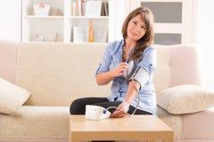 Kobieta sprawdza jej ciśnienie krwi Zdjęcia Stock