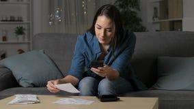 Kobieta sprawdza kwity na telefonie w domu zbiory wideo