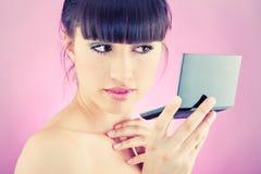 Kobieta sprawdza twarzy skórę w lustrze fotografia stock