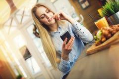 Kobieta sprawdza wiadomość w ogólnospołecznych sieciach na twój telefonie w wygodnej kawiarni w stylu Provence Obrazy Stock