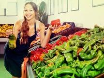 Kobieta sprzedawca jest ubranym fartucha mienia zieleni i czerwieni paprykę Zdjęcia Royalty Free