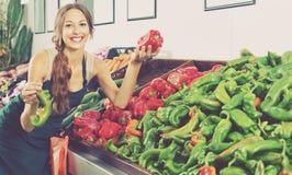 Kobieta sprzedawca jest ubranym fartucha mienia zieleni i czerwieni paprykę Obrazy Stock