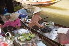 Kobieta sprzedawcy sprzedaje jedzenie od ich łodzi w Spławowym rynku Fotografia Stock
