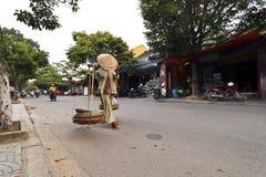 Kobieta sprzedawcy ulicznego odprowadzenie w drodze w hoi Vietnam fotografia royalty free
