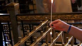 Kobieta Stawia świeczkę w kościół chrześcijańskim zbiory