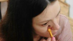 Kobieta stawia Fundacyjną tonalną śmietankę na twarzy używać muśnięcie przed lustrem Zbliżenie kobiety ` s twarzy odgórny widok zbiory