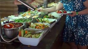 Kobieta stawia jedzenie na jej talerzu od bufeta przy hotelem zbiory