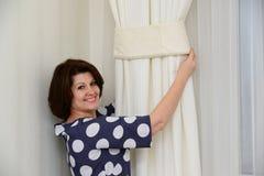 Kobieta stawia kahaty na zasłonach Obrazy Royalty Free