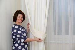 Kobieta stawia kahaty na zasłonach w mieszkaniu Fotografia Stock