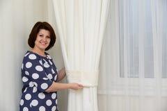 Kobieta stawia kahaty na zasłonach w mieszkaniu Zdjęcie Stock