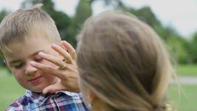 Kobieta stawia ochronną śmietankę na chłopiec twarzy chłopiec no lubi go, on obraca daleko od zdjęcie wideo