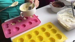 Kobieta stawia rozciekłą białą czekoladę w krzem foremce Dla natłuszczenia ściany forma Kulinarny deser zbiory