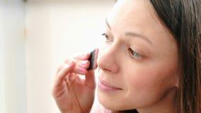 Kobieta stawia rumiena na twarzy z muśnięciem przed lustrem zbiory wideo