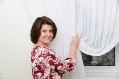 Kobieta stawia tiulowych kahaty na zasłonach w mieszkaniu Obraz Stock