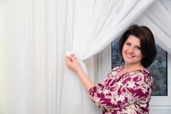 Kobieta stawia tiulowych kahaty na zasłonach w mieszkaniu Zdjęcie Royalty Free