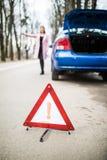 Kobieta stawia trójboka na drodze, samochodowy kłopot próbuje zatrzymywać pomoc i dostawać od innego kierowcy od drogi Zdjęcia Royalty Free