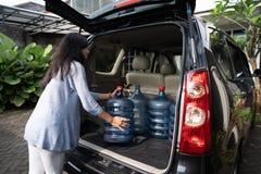 Kobieta stawia wodnego galon w samochodowym bagażniku zdjęcie royalty free