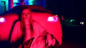 Kobieta stoi bezczynnie samochód w białej panny młodej sukni w zmroku przy zaniechanym domem z nieżywym panna młoda makijażem dla zbiory