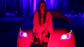 Kobieta stoi bezczynnie samochód w białej panny młodej sukni w zmroku przy zaniechanym domem z nieżywym panna młoda makijażem dla zdjęcie wideo