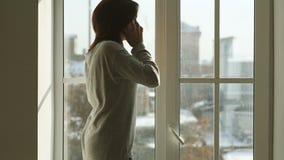 Kobieta stoi blisko szerokiego okno z smartphone zbiory wideo