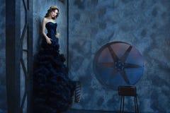Kobieta stoi ciemnego pokój w długiej czerni sukni Zdjęcie Royalty Free