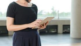 kobieta stoi pastylka komputer i u?ywa w budynku obrazy royalty free