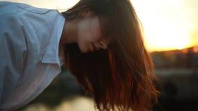 Kobieta stoi, pochyliła się i patrzy na wodę o zachodzie słońca zbiory