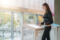 Kobieta stojaki, dotyka cyfrowy pokaz podczas gdy trzymający smartphone Nowatorskie technologie, cyfrowy pokaz, miastowa nawigacj Obrazy Royalty Free