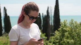 Kobieta stojaki na wybrzeżu z smartphone zdjęcie wideo