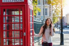 Kobieta stojaki obok czerwony telefoniczny budka w Londyn i rozmowy na telefonie komórkowym zdjęcie royalty free