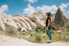 Kobieta stojaki obok pięknych skał i podziwiają krajobraz w Cappadocia w Turcja Krajobraz Zdjęcia Royalty Free