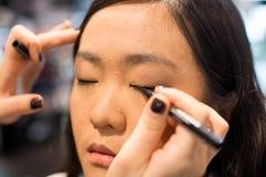 Kobieta stosuje kosmetyki Obrazy Royalty Free