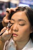Kobieta stosuje kosmetyki Zdjęcia Royalty Free