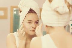 Kobieta stosuje maskową śmietankę na twarzy w łazience fotografia stock