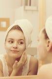 Kobieta stosuje maskową śmietankę na twarzy w łazience zdjęcie stock