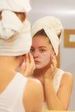 Kobieta stosuje maskową śmietankę na twarzy w łazience obrazy stock
