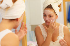Kobieta stosuje maskową śmietankę na twarzy w łazience obraz royalty free
