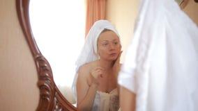 Kobieta stosuje maskową nawilżanie skóry śmietankę na twarzy patrzeje w lustrze zbiory