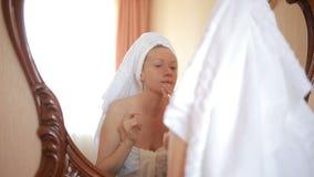 Kobieta stosuje maskową nawilżanie skóry śmietankę na twarzy patrzeje w lustrze zbiory wideo