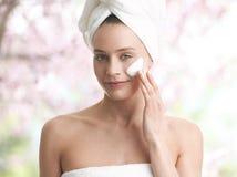 Kobieta stosuje moisturizer śmietankę na twarzy Obrazy Stock
