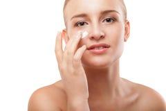 Kobieta stosuje moisturizer śmietankę na twarzy odizolowywającej Fotografia Stock