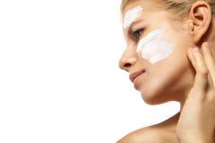 Kobieta stosuje moisturizer śmietankę na twarzy odizolowywającej Zdjęcia Royalty Free