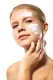 Kobieta stosuje moisturizer śmietankę na twarzy odizolowywającej Obrazy Stock