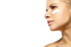 Kobieta stosuje moisturizer śmietankę na twarzy odizolowywającej Obrazy Royalty Free