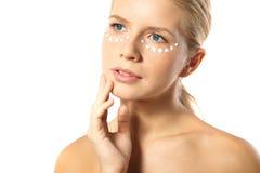 Kobieta stosuje moisturizer śmietankę na twarzy odizolowywającej Zdjęcia Stock