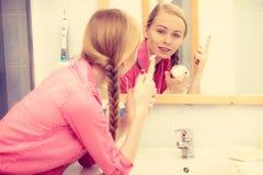 Kobieta stosuje nawilżanie skóry śmietankę Skincare fotografia stock