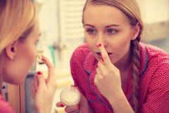 Kobieta stosuje nawilżanie skóry śmietankę Skincare fotografia royalty free