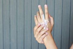 Kobieta stosuje ręki kremowe Fotografia Stock