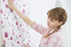 Kobieta stosuje tapetę na ścianie w nowym domu zdjęcia stock